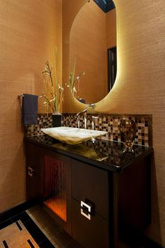This warm, Asian-inspired bathroom features a dark wood vanity with stone countertops and a multicolored tile backsplash, a marble vessel sink and a back-lit oval mirror. The eclectic gold wall treatments really give this space a zing!