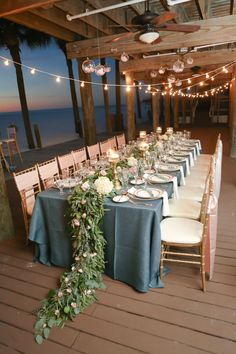 Bohemian Glam Beach Wedding with Navy Blue Burlap Linens and Floral Garland Centerpieces on Long Feasting Tables at Clearwater Beach Wedding Venue Hilton Clearwater Beach | Linens by Over The Top Rental Linens | China/Glassware by A Chair Affair | Gold Chiavari Chairs and Beaded Glass Chargers from Signature Event Rentals