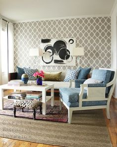 Fantastic contemporary living room design with white & gray moorish tiles wallpaper accent wall, black & white abstract art, white sheers with black ribbon trim, wool rug layered over jute herringbone rug, white chair upholstered in blue fabric, wood sofa with oatmeal linen cushions and glossy white lacquer cocktail table.