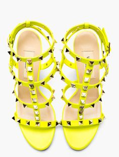 Buffed leather multi-strap heeled sandals in neon yellow by Valentino. Pale gold-tone hardware. Signature pyramid stud embellishments throughout.  http://www.zocko.com/z/JJXCX