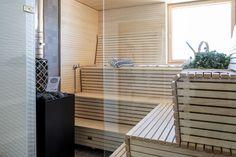 Tilavaan saunaan lämpöä tuo komea kiuas. Lisää tilantuntua tuo lasiseinä.
