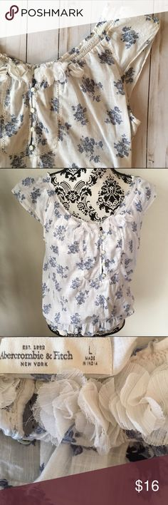 "Abercrombie & Fitch peasant blouse Romantic loose fit blouse. Blue floral on white cotton woven fabric. White fabric roses & Little white buttons adorn elastic neckline. Cap sleeves & elastic waist. Measurements laying flat: 20 inches armpit to armpit, elastic waist 13 inches stretching to 20"", length 23 inches. Excellent condition Abercrombie & Fitch Tops"