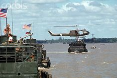 January Vietnam --- US Navy amphibious landing craft cross a body of water escorted by helicopter cover. --- Image by © Tim Page/CORBIS Vietnam History, Vietnam War Photos, American Civil War, American History, British History, Native American, Brown Water Navy, Landing Craft, War Image