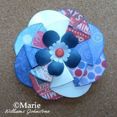 Decorating the paper rosette with red, white and blue embellishments for the 4th July