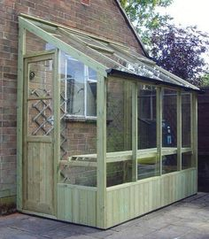 Lean to greenhouse made with reclaimed wood & old windows.