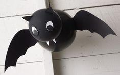 Murciélagos para Halloween: Inflar 2 globos, uno más que el otro. El más pequeño será la cabeza. Unir entre sí los globos por la zona de los nudos con cinta adhesiva. Dibujar en cartulina negra las alas del murciélago, recortalas y pegalas en el globo más grande. Será más fácil, para pegarlas después, que dejemos algunas pestañas en las alas. Ahora dibujamos y recortamos, en cartulina color blanca, los ojos y los colmillos del murciélago. Pega estos rasgos en el globo más pequeño. X