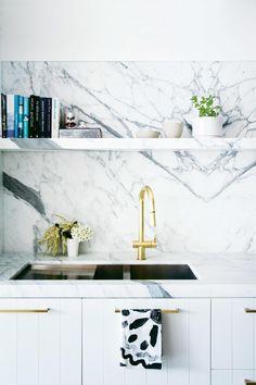 Calacatta marble, brass tapware, brass handles, vertical panelled cabinet doors, floating shelf
