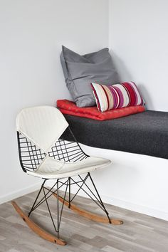 Red and grey built-in bed with vintage rocker