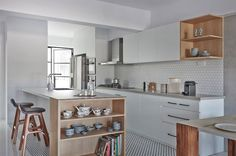 Open-concept kitchen with Moroccan floor tiling that stands out against the white compressed marble flooring in the living and dining rooms. Wood accents are skilfully integrated within the open wall shelves.
