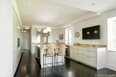 White kitchen design with dark wood floors and natural touched