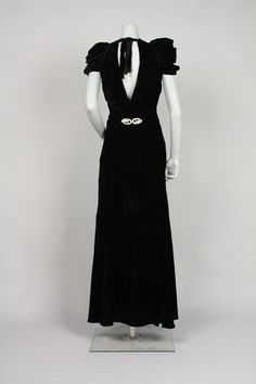 """Dress Accession Number: 2001.104.129 Date Made: 1932-1936 Description: Dress; black velvet gown, v-neckline in back, puff sleeves, attached belt w/ rhinestone buckle. Full length dress has a high, softly draped neckline in front, tapering in back to a deep """"V"""" at the waist. Short, wide self-fabric ties hold the neckline together at center back. Short sleeves are heavily gathered, giving an exaggerated puffiness at the shoulder."""