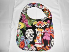 Sugar Skeletons Bib - I've always had trouble with my kids drooling through bibs. This bib solves that problem. Underneath the decorative cotton is a layer of terry and a layer of PUL, to keep baby's clothes clean and dry. It also has snaps to adjust for 3 different sizes around the neck as baby grows and is long enough to protect against toddler messes, too.This particular bib features a 100% black cotton fabric with sugar skulls and sugar skeletons all over. It has heart shaped white…