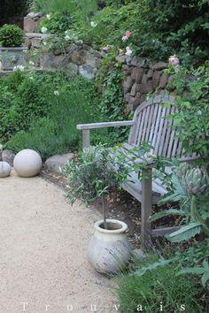 Spring garden - cement spheres & artichokes add exciting elements to this garden