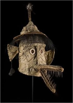 Kovave Spirit mask from Papua New Guinea  Many of the masks are feats of construction and conjuring. Consider a spirit mask from Papua New Guinea used in male initiation rites; it is made mostly of tapa cloth, reeds, grasses and seed pods, with its conical hat, wide ears and long, wolflike snout toothed with sharp nails. Or an Eskimo shaman's mask made of wood, wire and feathers. Its stern face, with the black goatee and curled mustache of a dime-novel villain, is encircled by two rings of…