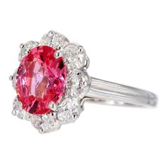 Platinum cluster ring consisting of 1 oval shaped Padparadscha sapphire weighing 2.43 carats, surrounded by 1 row of oval brilliant cut diamonds having a total weight of 2.50 carats, signed Oscar Heyman. 1stdibs.com.