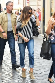 Sarah Jessica Parker wears a striped oversized shirt with cuffed boyfriend jeans, suede ankle boots, and a black bag.