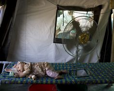 An infant dozes on a stretcher in a fan-cooled tent at the MSF run cholera treatment centre at the Mardan Medical Complex.