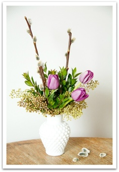Spring flowers - pussy willow branches. A few tulips nestled into bright green foliage with a base of seeded eucalyptus. By Living Fresh Flower Studio and School.