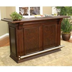 Host dinner parties and more for years to come with this timeless wood home bar. The bar is the right height for use with stools of your choice, and guests can relax their feet on the brushed steel footrest. The bar also features shelves and cabinets.