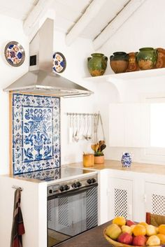 Beautiful kitchen oven backsplash with handmade clay ceramic pots that line the shelf near the ceiling and bring texture, color, and individuality to the space.