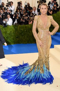 Blake Lively in Atelier Versace at the Met Gala 2017.  She wore a gold gown comprised of delicate gold chains with multi-color feather accents cascading down the train in a dégradé fashion from gold to ocean blue.