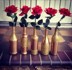 DIY spray painted wine bottles. Gold spray paint and gold glitter! Just tape the section you want to glitter and use mod podge before and after you apply glitter!