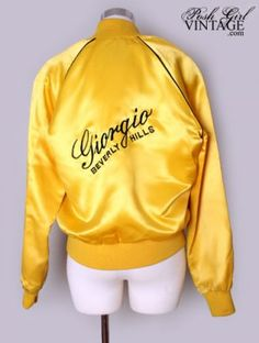 """Here is a vintage, late 70's early 80's, gold yellow satin jacket from the Giorgio Of Beverly Hills Signature line. It has the logo on the back and chest with black piping. Cuffs and waist are stretchy sweater like material. Zips up the front. Lined in yellow. Easy care hand washable. Very popular during the Studio 54 craze. Vintage designer chic!We have LAY-A-WAY!- See """"Ordering + Lay Away"""" page for details.Condition Details: No holes or stains. General Minor Wear. There is a small pen…"""