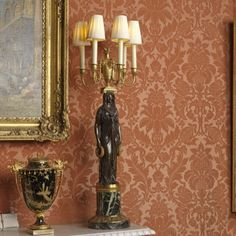 Located 2015 in the Picture Gallery of Buckingham Palace, London, UK. 1 of a Pair of candelabra made by Thomire & Delcambre. 5-light candelabra of Gilt bronze on base of green marble with Gilt moulding. A draped female figure holds a floral wreath in each hand & a flaming urn on her head. A band around the urn are the 5 candle arms & 3 bearded masks. Bought by King George IV (1762-1830) UK in 1814, Uncle of Queen Victoria (1819-1901) UK.
