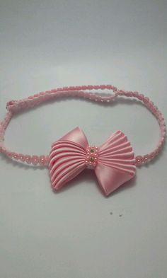Laço na cor rosa bebe, na faixa elastica com perolas, e regulagem de tamanho de recem nascido ate 1 ano. O laço tenhe aproximadamente 6,5 cm.