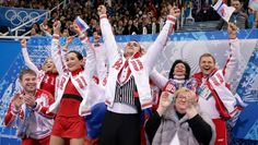 Russian figure skaters Ksenia Stolbova and Fedor Klimov celebrate with their teammates