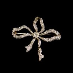 Edwardian 14 k gold with platinum facing bow pin with center diamond (.72 ct) and 66 round cut accent diamonds. $5,250.00 | Haig's of Rochester Fine Jewelry & Objects of Art, Rochester, MI.