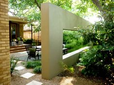 While the wall was built as a frame of reference and garden partition, Frank says the designers have been excited to hear how it has evolved as a garden feature. The children play behind and on it, and use it as a place to sit and hang out.  The moviewall bisects two distinct backyard spaces. The outdoor dining space on the front side is structured and well ordered.   by Studio Balcones