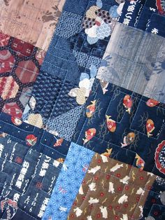 This quilt features many popular prints imported from Japan and featuring traditional motifs such as dragonflies, bunnies, fish, parasols and calligraphy. The main colors are dark navy blue and soft, warm brown with accents in shades of red and beige. The quilt pattern is called Bits and Pieces and designed by Mountainpeak Creations. My retired store sample is being sold with permission. Details of the lovely professional machine quilting can be seen in the closeup photo. The quilt measures…