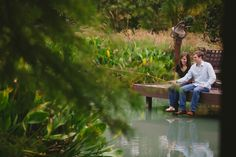 Outdoor engagement photos with couple sitting on a dock fishing - Photo by Laura Elizabeth Photographers