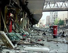 Postbox outside wrecked Marks & Spencer store after 1996 city centre bomb in Manchester (Archive BBC footage).
