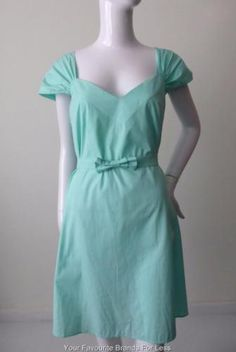 Miu-Miu-Dress-Size-IT-44-AU-14-US-10-Green-Made-in-Italy-rrp-1446-00 Cotton is the most comfortable material to wear on those hot, summer days. This Miu Miu dress is made from 100% cotton in a pretty aqua colour. It has a V neck-line with wide pleated shoulder straps. The skirt section is slightly flared. The waist is highlighted with a self styled belt which has an attached front bow. It is a size 44 and should fit a size AU 14 or US 10.  Made in Italy.