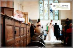 Bored little boy in Croft Castle Church, Herefordshire with bride and groom at the altar in the background