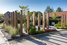 Deze voorbeeldtuin is open en tegelijk besloten. Het gras, de beplanting, de houten balken, de keramische tegels met hout-effect: u heeft uw eigen strandgevoel te pakken. Inclusief rustig kabbelend water op de achtergrond.