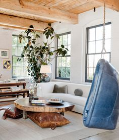 modern furniture with a touch of rustic wood in a loft-like living room - and that blue chair!