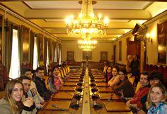 """Alumnos de Escuela Europea durante la visita al """"Salón de Plenos"""" del Ayuntamiento de Oviedo, sentados como concejales."""