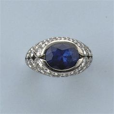 A SAPPHIRE AND DIAMOND DRESS RING  Set with an oval cut sapphire within an openworked mount pavé-set with brilliant-cut diamonds