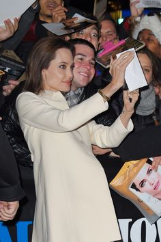 Taking a selfie with a fan outside The Daily Show in December 2014.   - ELLE.com