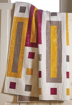 This modern style bed size quilt in gray, red and yellow fabrics is easy to make and a great pattern for a beginner quilter.