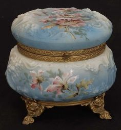 Wonderful large covered box made by the C. It has a fancy brass rim around the top and base. The box has a raised surface and is decorated with a floral design on a light.