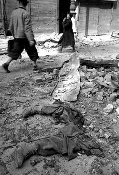 Vienna, 1945: Civilians rush by what remains of a German soldier (judging from the boots) after he was obliterated by an explosion (?) or direct cannon fire (?) By then, the value of life was nil....