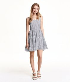 Sleeveless dress in cool, woven fabric with a printed pattern. Low-cut neckline with ties at back joining shoulder straps. Seam at waist and flared, tiered skirt.