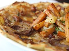 ROAST DUCK POUTINE PIZZA. CURDS, FRIES, CARAMELIZED ONIONS, DUCK.