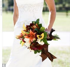 Bouquet of roses, calla lilies, tiger lilies, and greenery wrapped in chocolate-brown ribbon.    I like the mix of fall colors in the bridal bouquet.