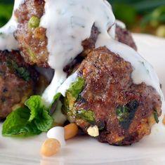 Closeup photo of Lebanese Meatballs on a plate with yogurt sauce.