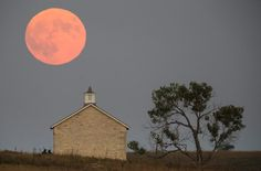 A super moon rises over the Lower Fox Creek School near Strong City, Kan., Sunday, Sept. 27, 2015. It was the first time Sunday since 1982 that a total lunar eclipse was combined with a Supermoon. (Travis Heying / The Wichita Eagle)